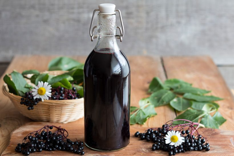 picture of elderberry syrup with elderberries and flowers on wooden plank.