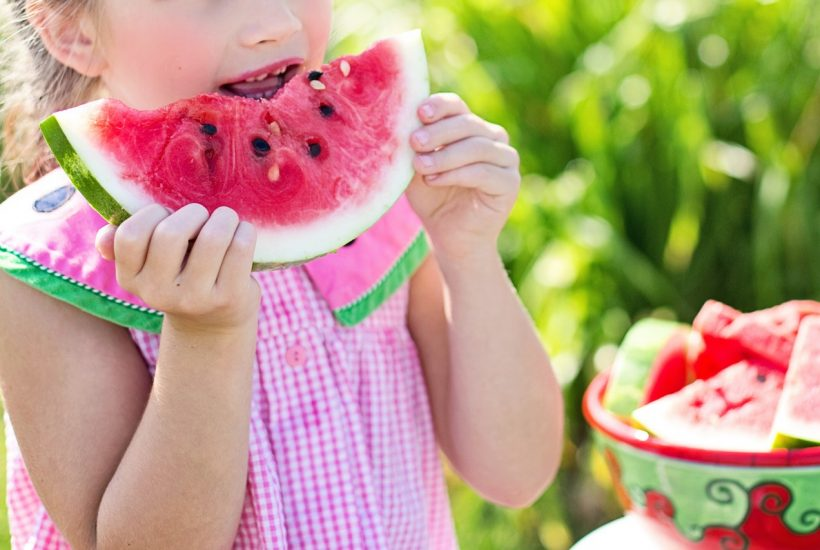 kid eating watermelon as a healthy alternative to the constant need for snacking