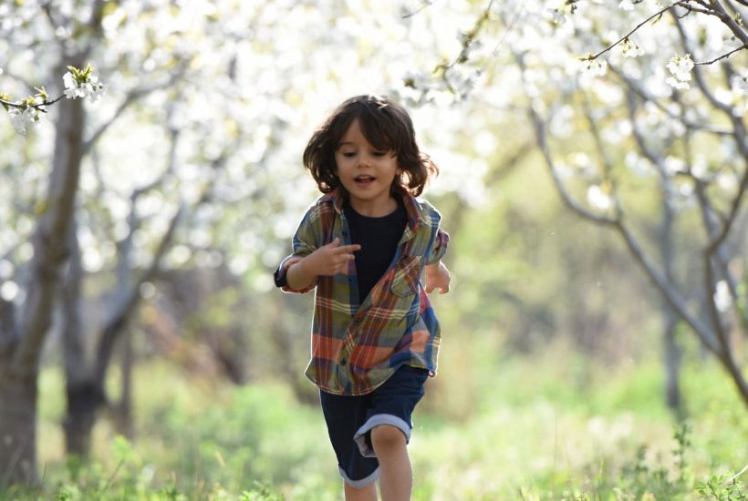 kid with a lot of energy running in a field