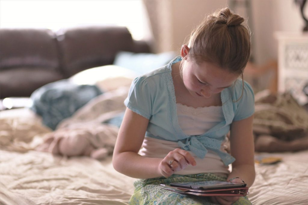 girl sitting on bed holding tablet
