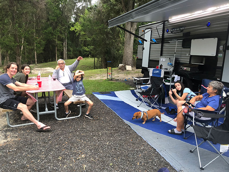 family enjoying RV life with camper and dog by a picnic table.